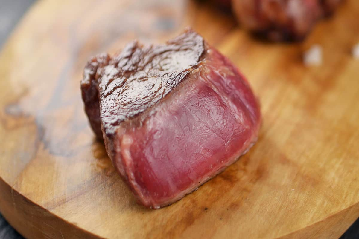 A cube of blue rare grilled steak on a wooden board