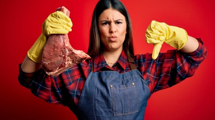 A woman in yellow gloves holding a gone bad steak, making a thumbs down gesture