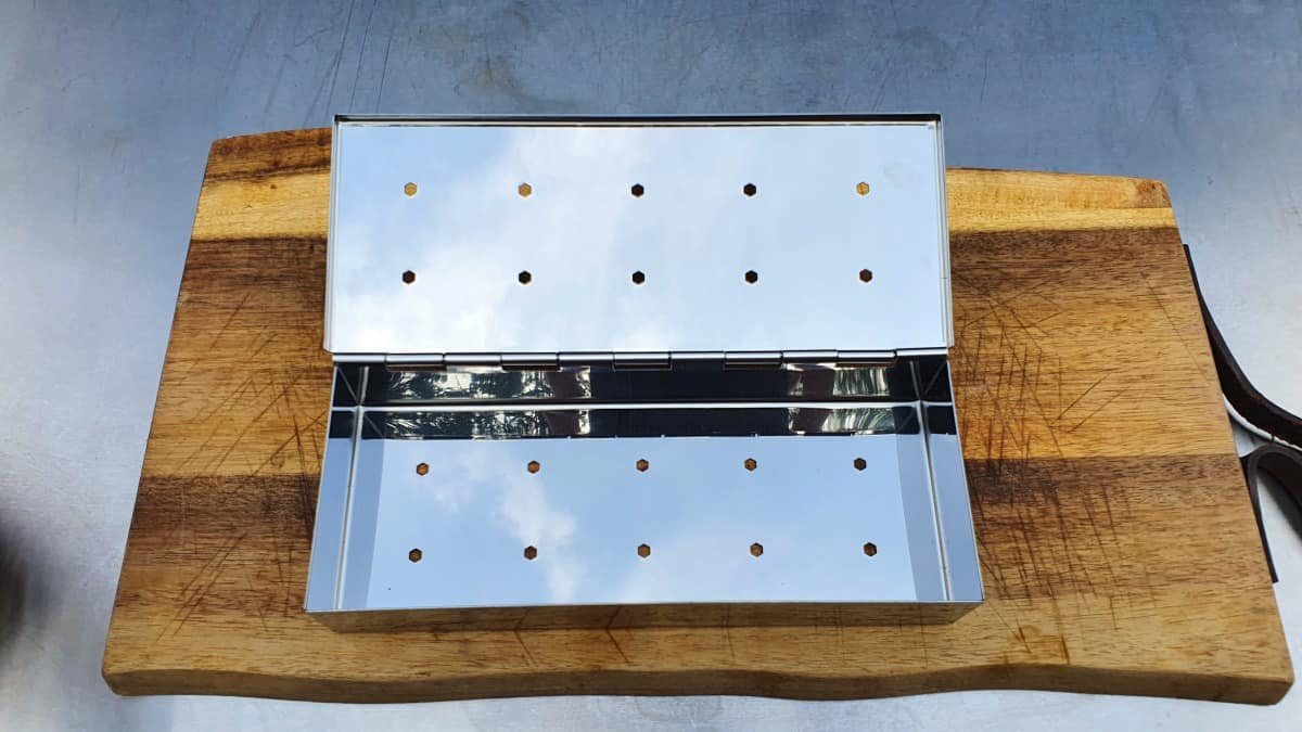 An empty smoker box with lid open, on a wooden cutting board