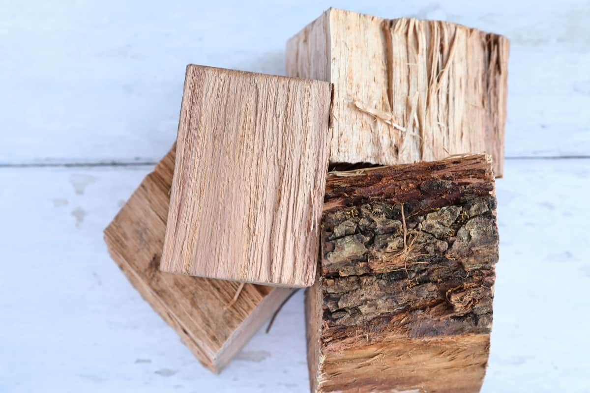 Four pecan wood chunks on a white wooden table