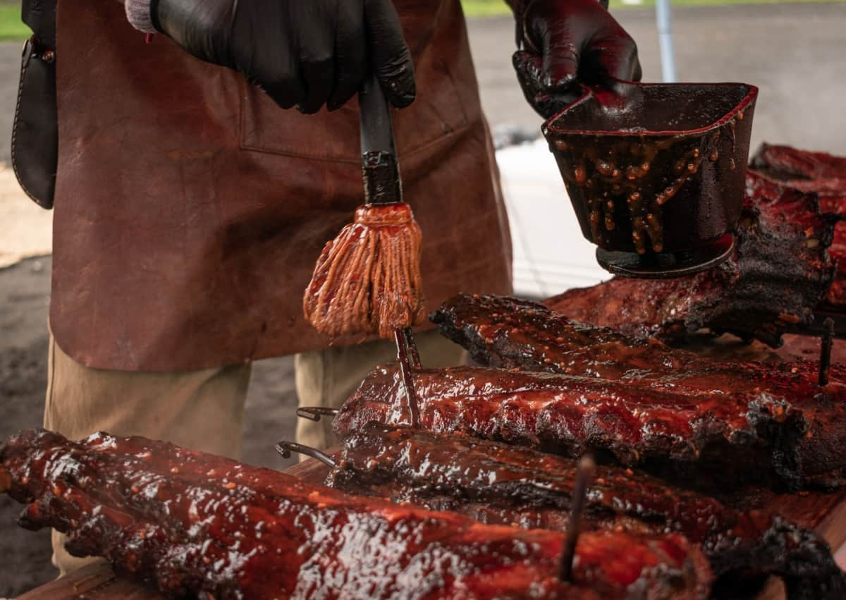 Many racks of ribs being mopped with sauce, by a man in a leather apron