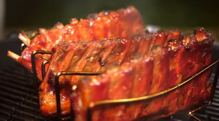 Three racks of ribs in a rack, being smoked in a charcoal smoker