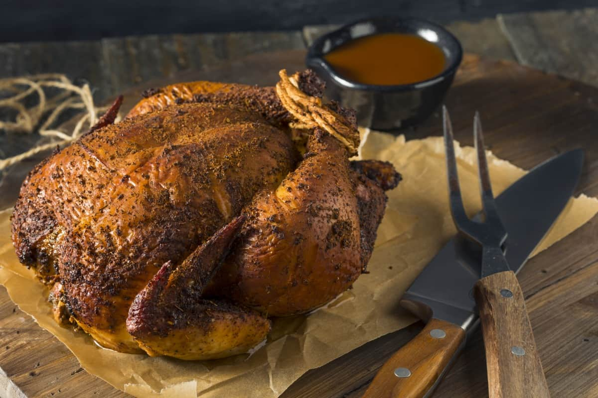 A smoked rubbed chicken on a cutting board about to be carved