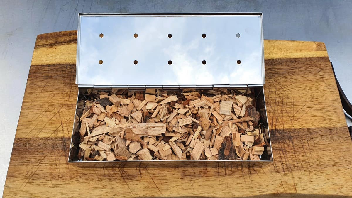 smoker box filled with wood chips, sitting on a cutting board
