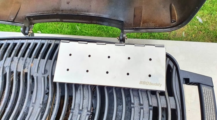 A silver smoker box on the grates of a portable gas grill