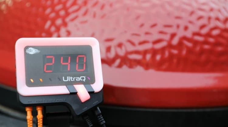 BBQ Guru UltraQ showing 240 F, sitting in front of a red kamado joe grill