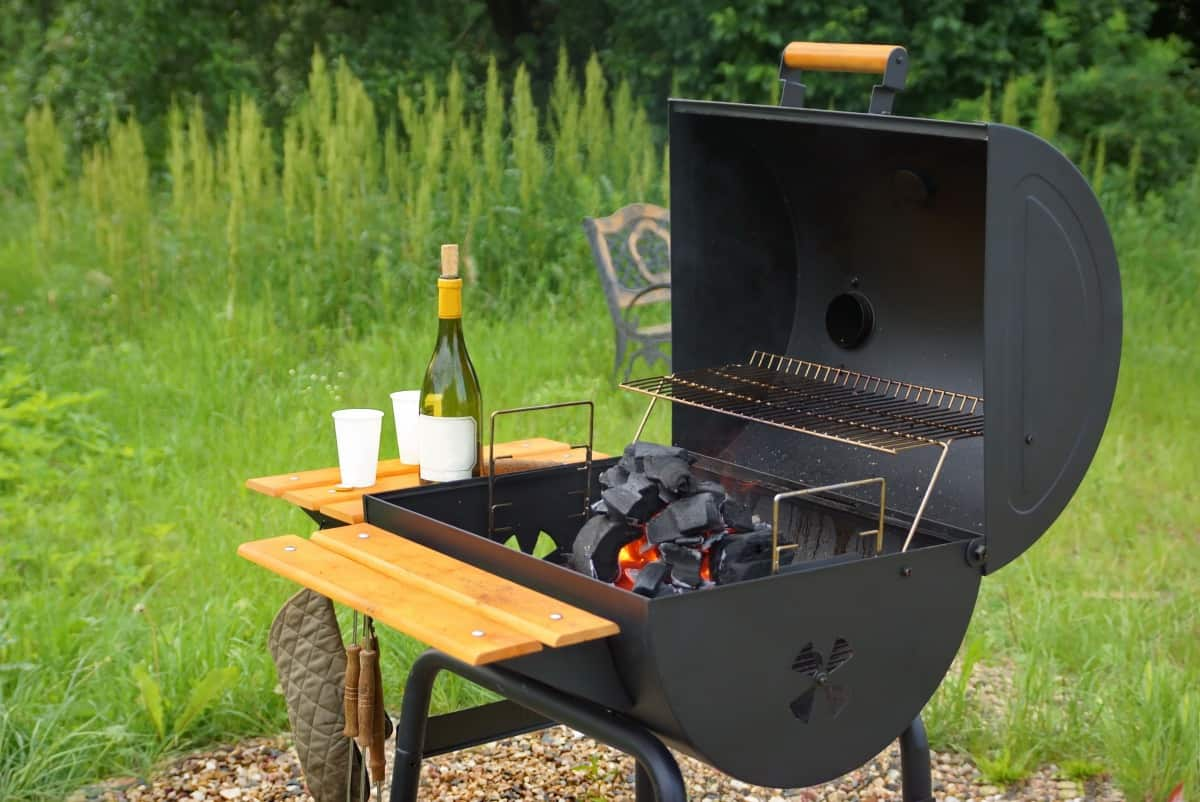 A barrel shaped charcoal grill with wooden side and front shelf, lid open and champagne on one side