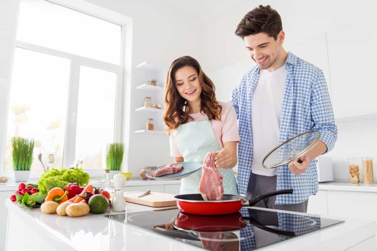 Man and woman dropping a large steak into a frying pan, in a well lit kitchen with fruit and veg laying around