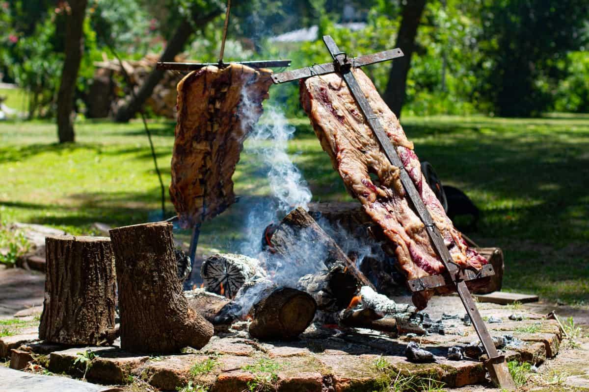 Grilling two lambs on crosses beside an open fire