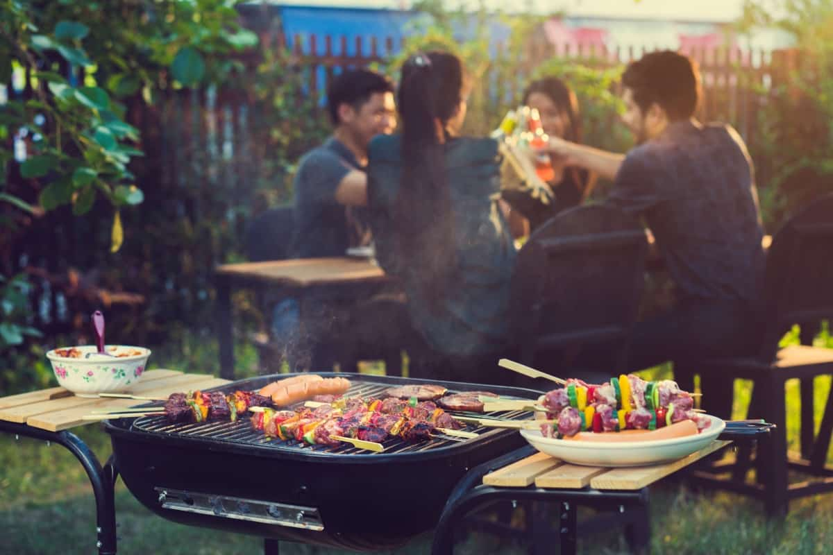 Foods cooking on an open grill, in front of a table of people dining outdoors