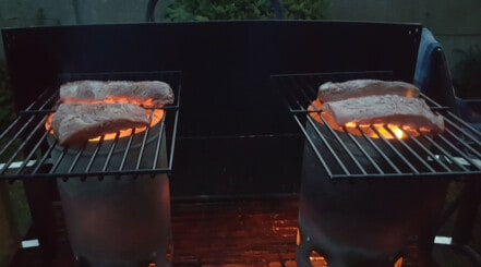 Afterburner steak grilling on top of two charcoal chimneys