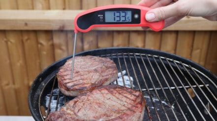 A red and black instant read thermometer reading 133.5 F in a steak