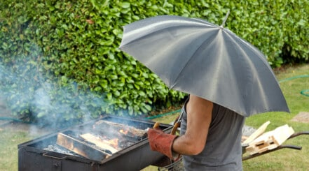 Man under an umbrella lighting a BBQ in the rain