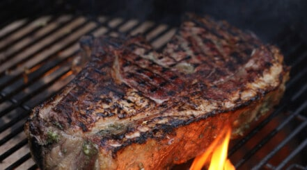 A bone in ribeye steak on a grill with flames licking around it