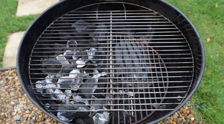 A weber kettle set up for two-zone grilling